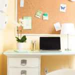 organized home office desk with bulletin board and potted plant