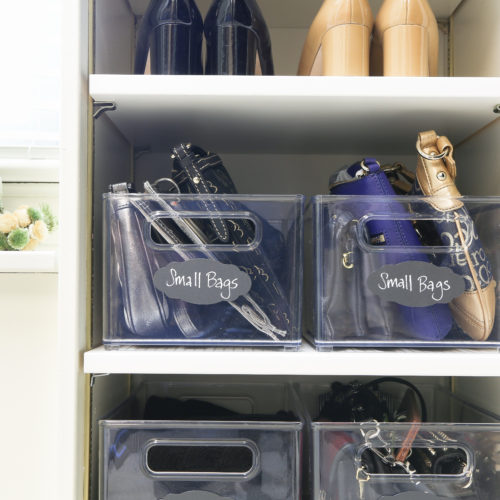 Clear bins holding small bags and purses inside closet