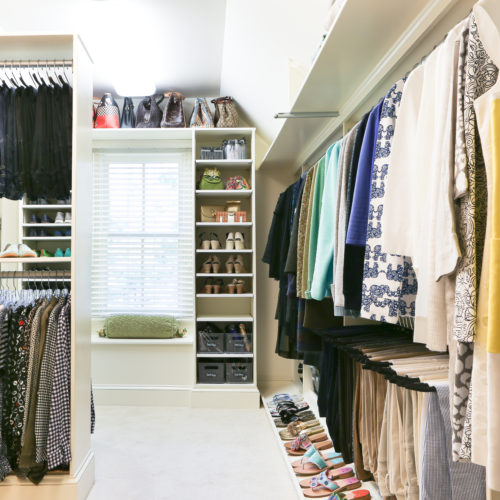 Bid closet with organized hanging clothes and lined up shoes