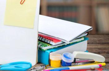 Piled art/school supplies on table