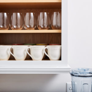 Organized glasses on shelves in cabinet