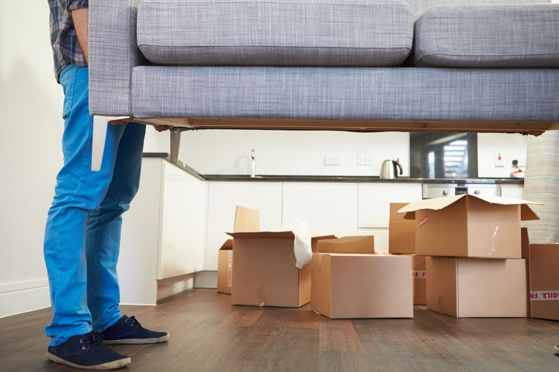 Man lifting couch with packed boxes in background