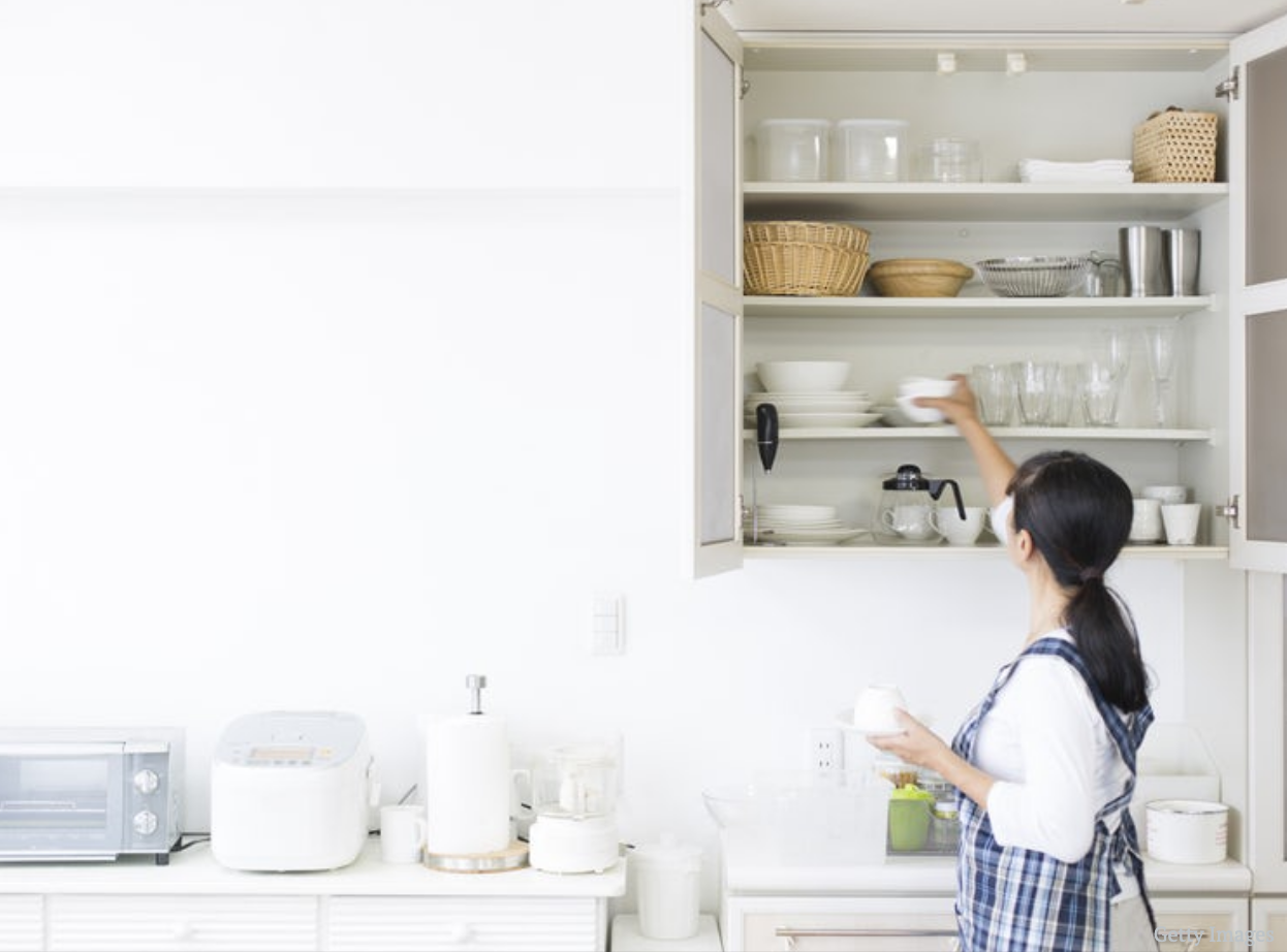 Woman Putting Dishes Away in Kitchen